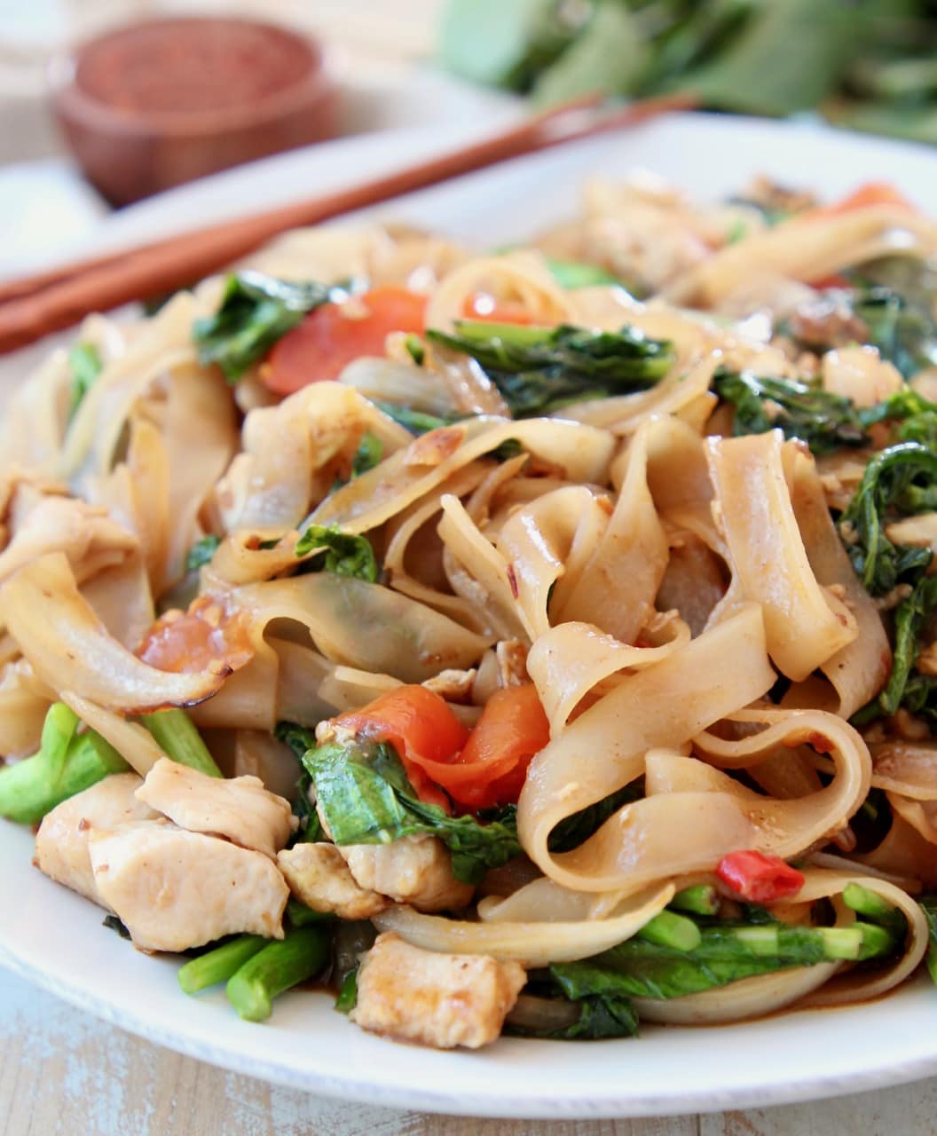 Thai wide noodles stir fried with Chinese broccoli on white plate