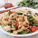 Drunken noodles with tomatoes and Chinese broccoli on white plate with chopsticks on the side