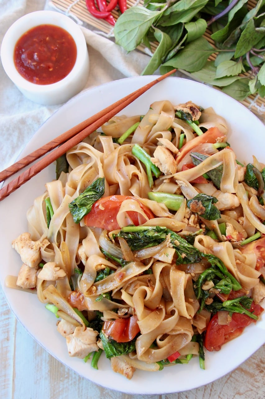 Overhead shot of Drunken Noodles on white plate with brown chopsticks on the side
