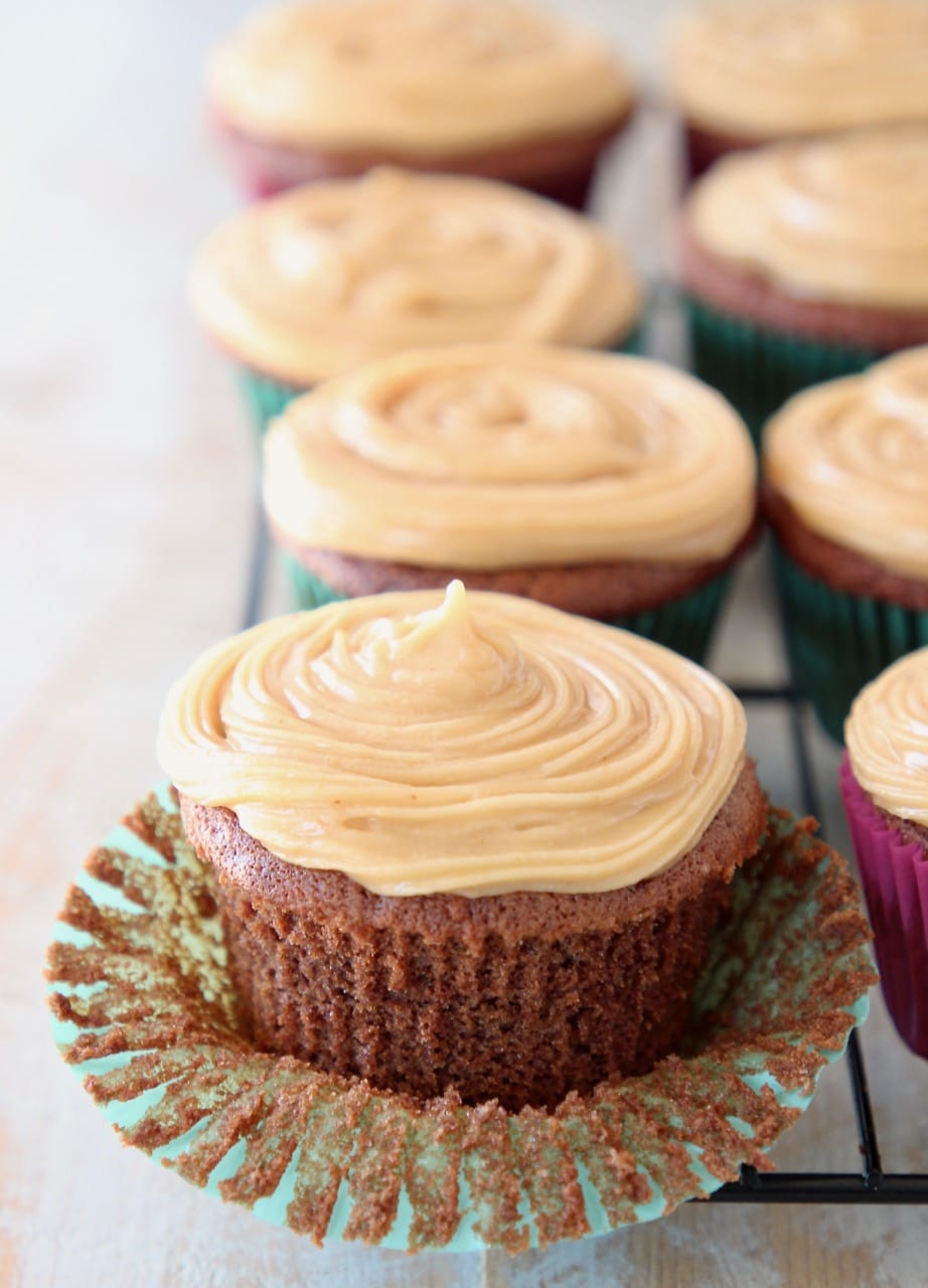 Chocolate cupcake with peanut butter frosting, sitting on cupcake liner, peeled from the cupcake