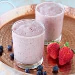 Fruit smoothie in glasses on copper tray with strawberries and blueberries