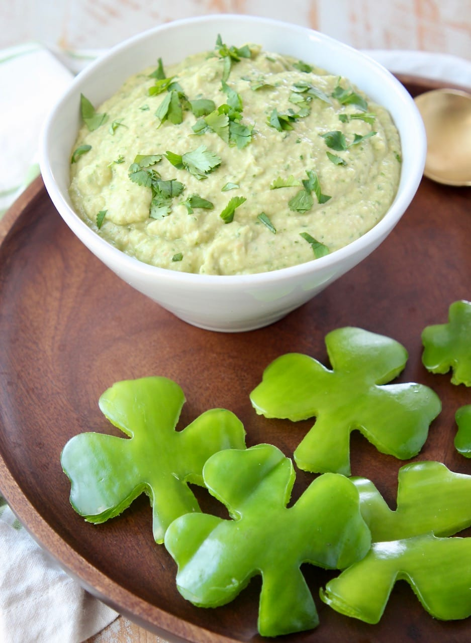 Spinach artichoke hummus in a white bowl on a wood serving tray with shamrock shaped green bell peppers