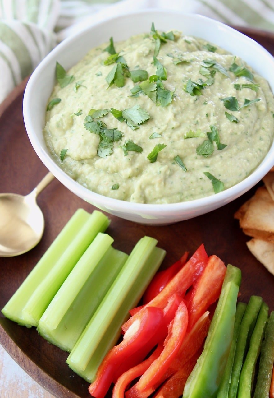 Spinach artichoke hummus in bowl with celery sticks, pita chips and bell peppers on the side