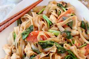 Overhead shot of drunken noodles on white plate with chopsticks on the side