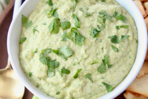 Spinach artichoke hummus in white bowl with gold and white spoon and pita chips on the side
