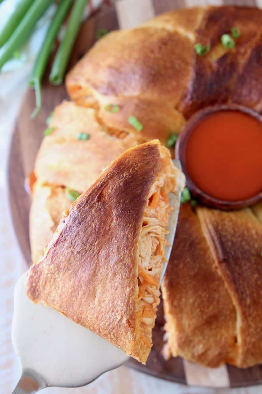 Slice of buffalo chicken crescent ring pulled out of the ring, sitting on a pie server