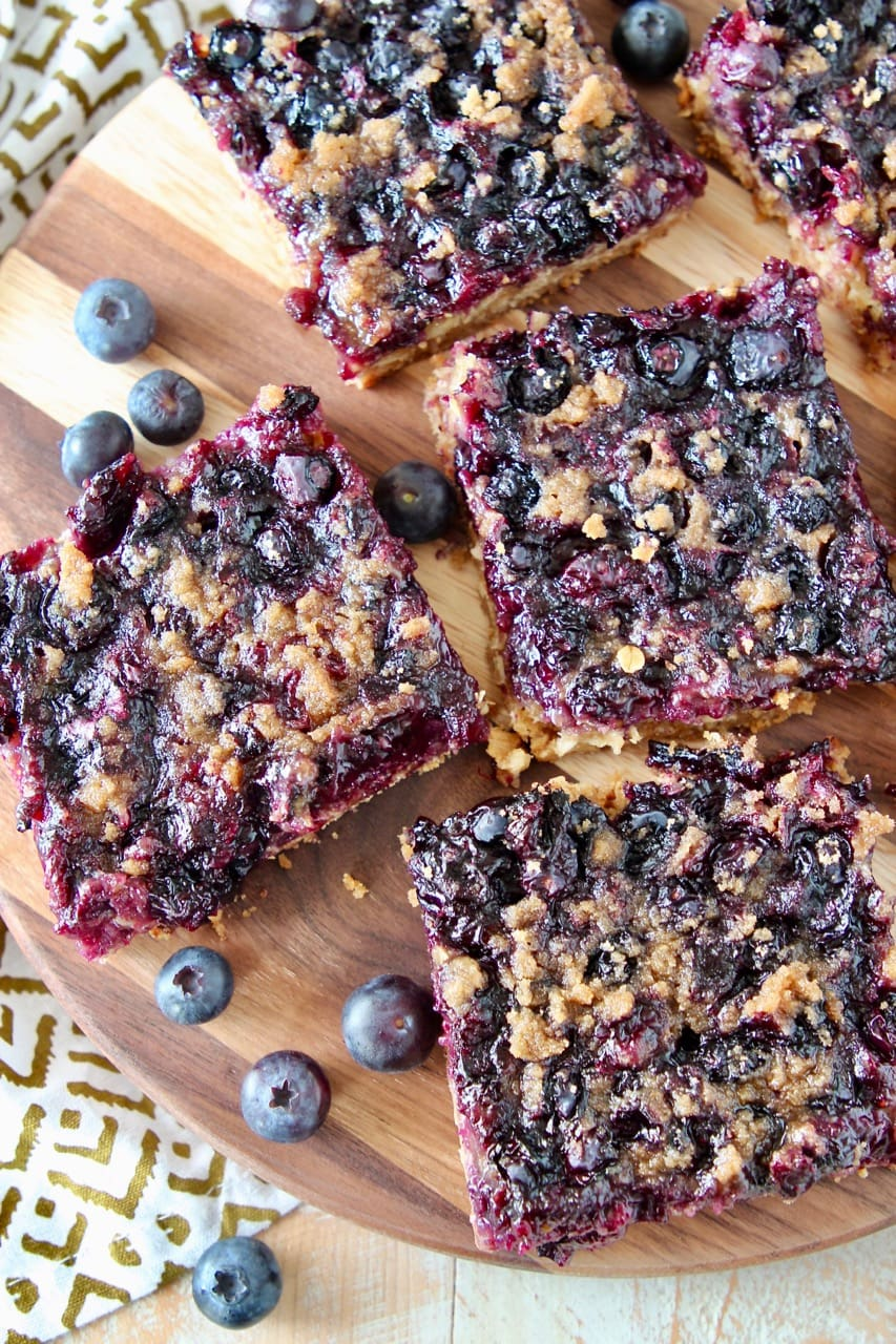 Blueberry oat bars cut into squares on wood cutting board with fresh blueberries