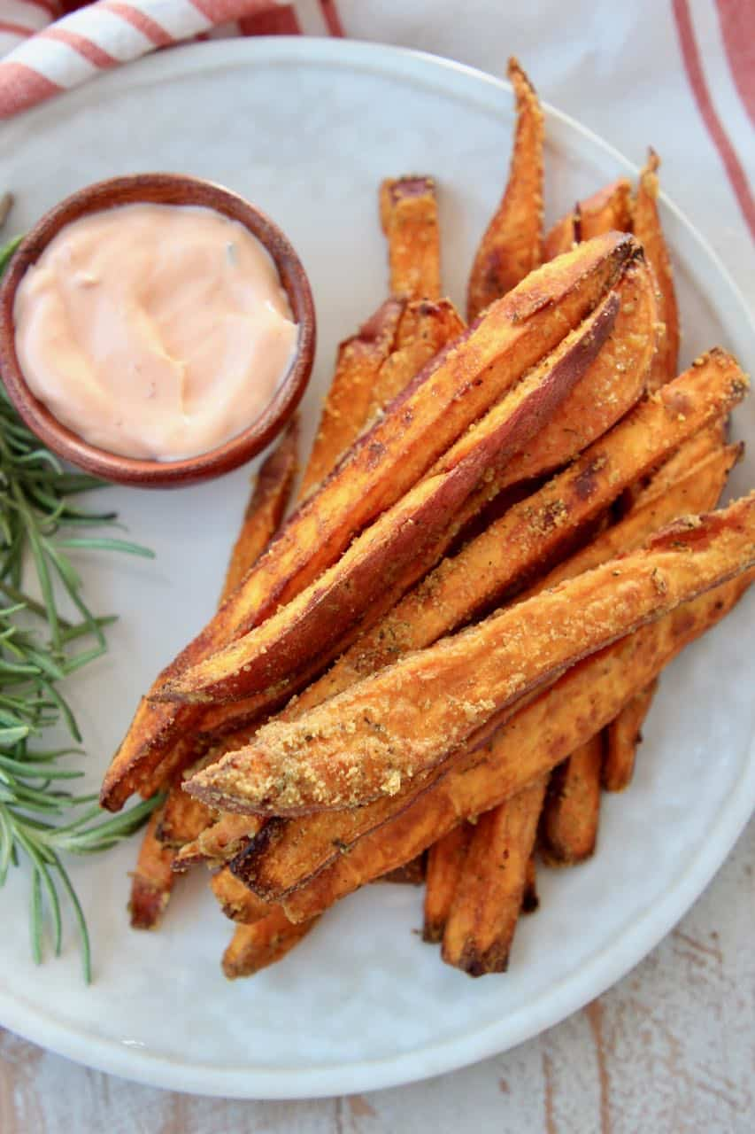 Sweet potato fries on plate with dipping sauce in a small bowl on the side