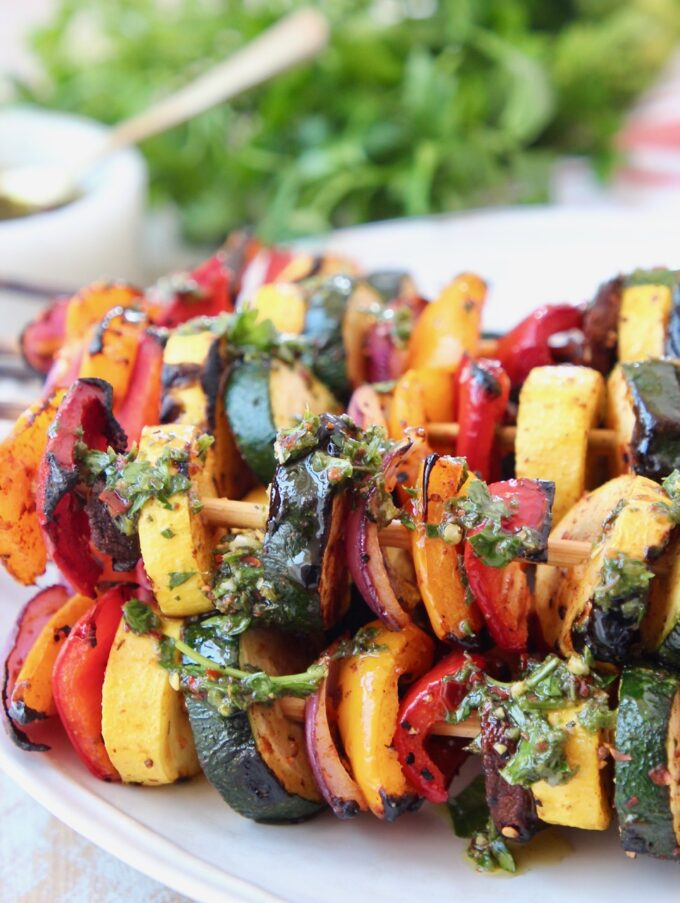 grilled vegetable skewers on plate with chimichurri sauce drizzled on top