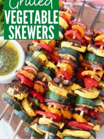 skewers of grilled vegetables on wood serving tray with chimichurri sauce on the side