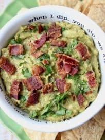 Guacamole in white bowl topped with cooked bacon, with tortilla chips on the side