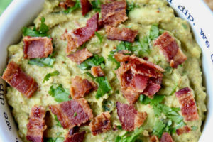 Guacamole in white bowl topped with cooked bacon pieces and fresh cilantro
