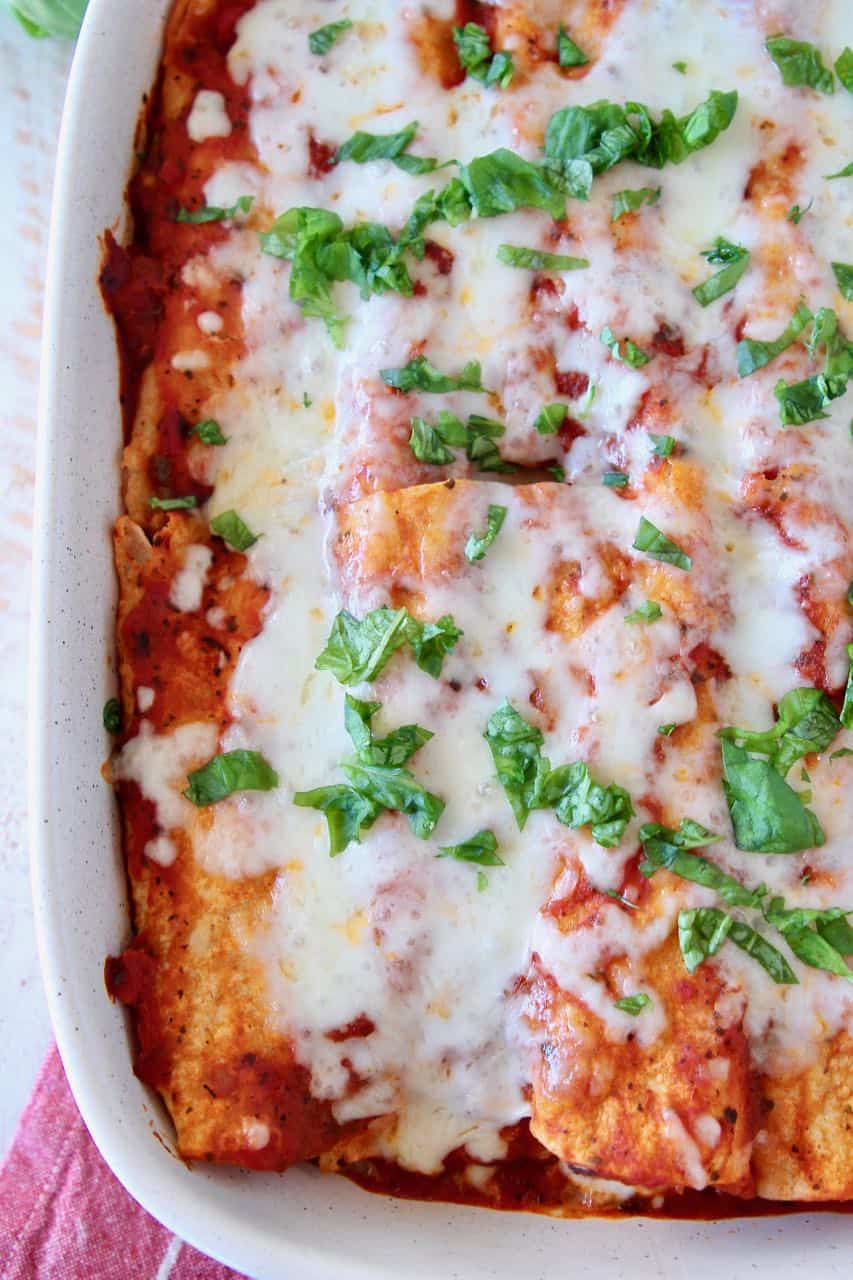 Overhead image of Italian enchiladas in baking dish topped with chopped fresh basil