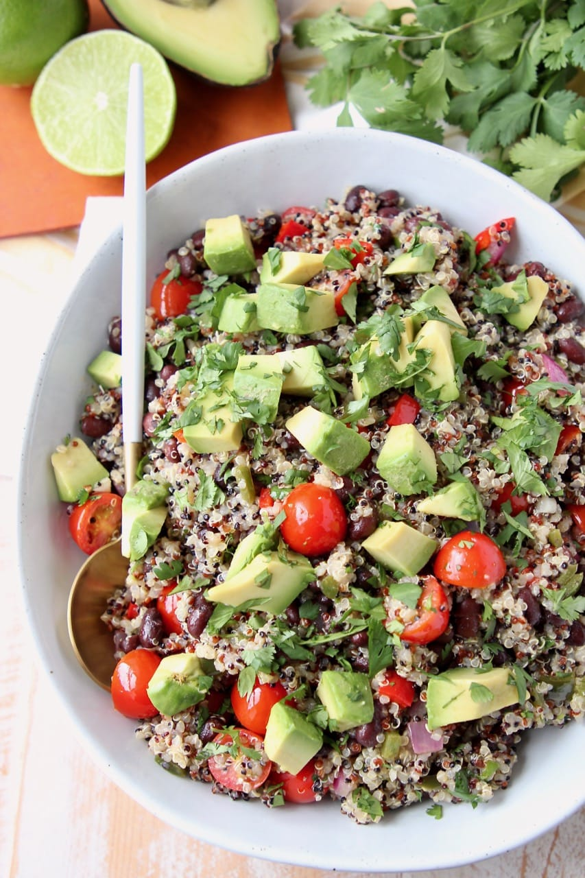 Overhead shot of quinoa salad in bowl with diced tomatoes and avocado