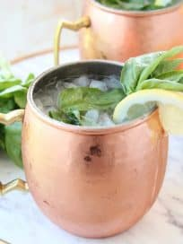 Copper mugs with moscow mules with fresh basil and lemon wedges