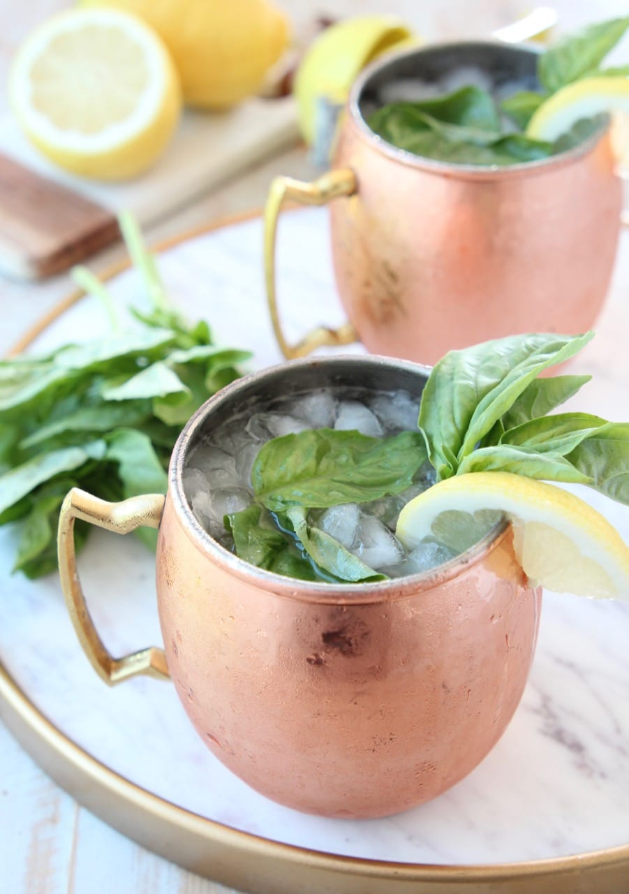 Moscow mule in copper mugs with fresh basil and lemon wedge on the side
