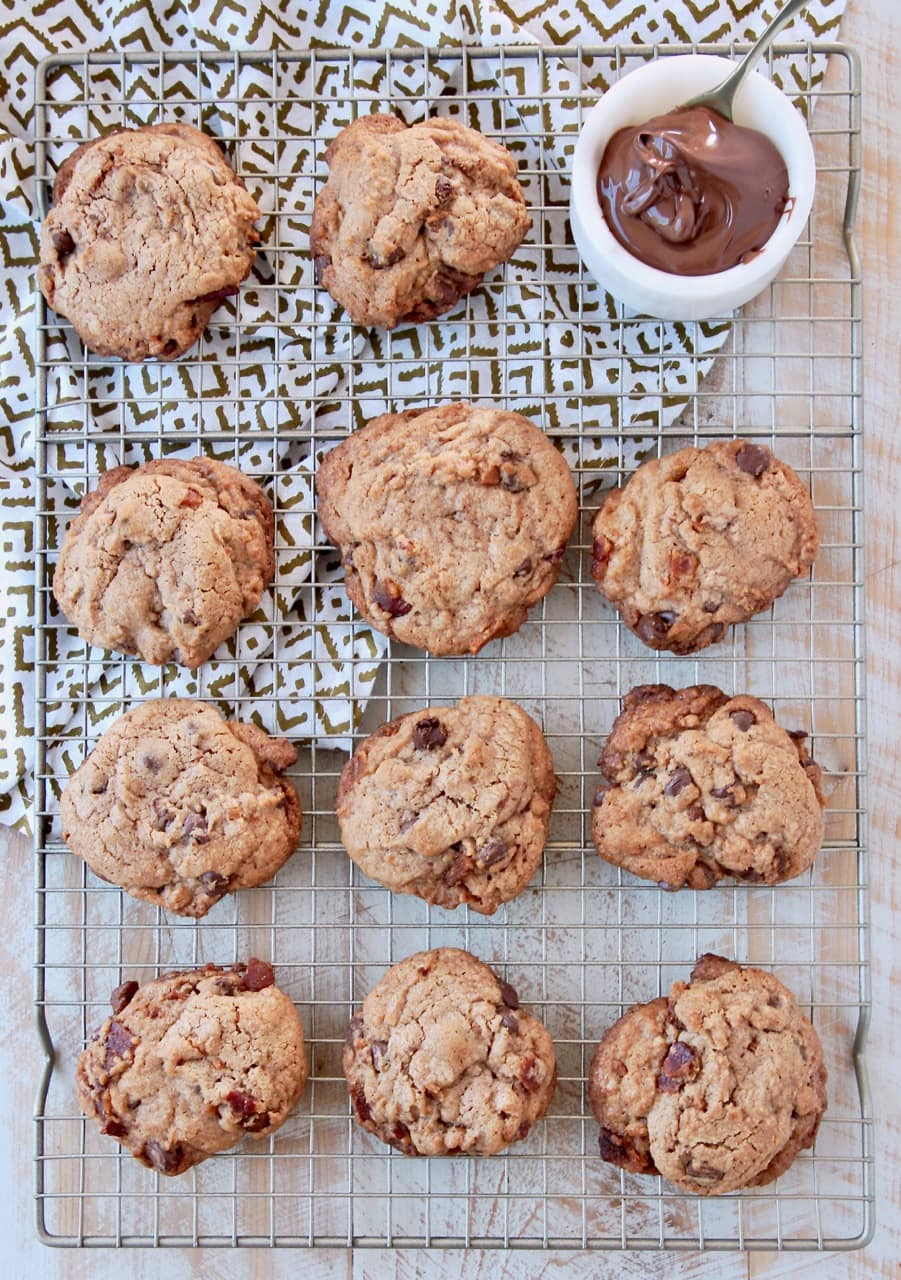 Bacon chocolate chip cookies on wire rack with towel underneath and bowl of nutella