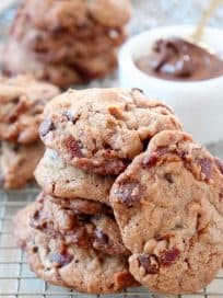 Bacon chocolate chip cookies stacked up on wire rack with bowl of nutella in background