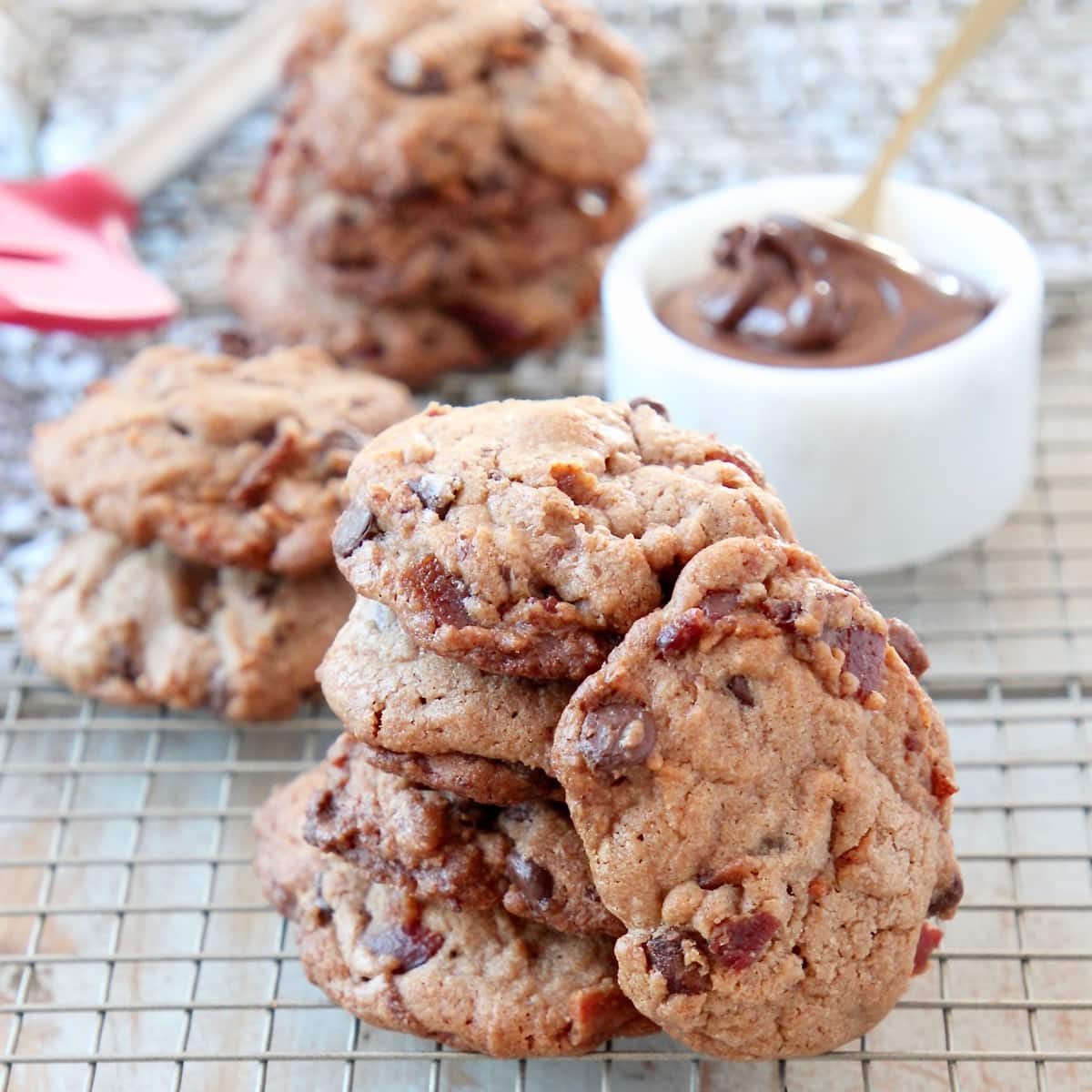 Bacon Chocolate Chip Cookies stacked up on wire baking rack with bowl of nutella