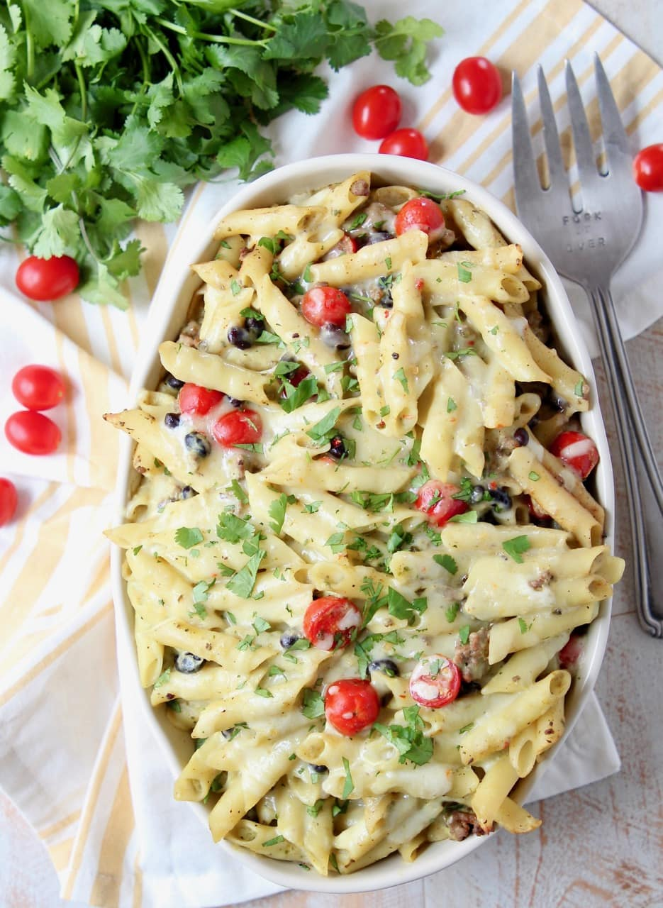 Taco pasta in large oval casserole dish with fork and cherry tomatoes on the side