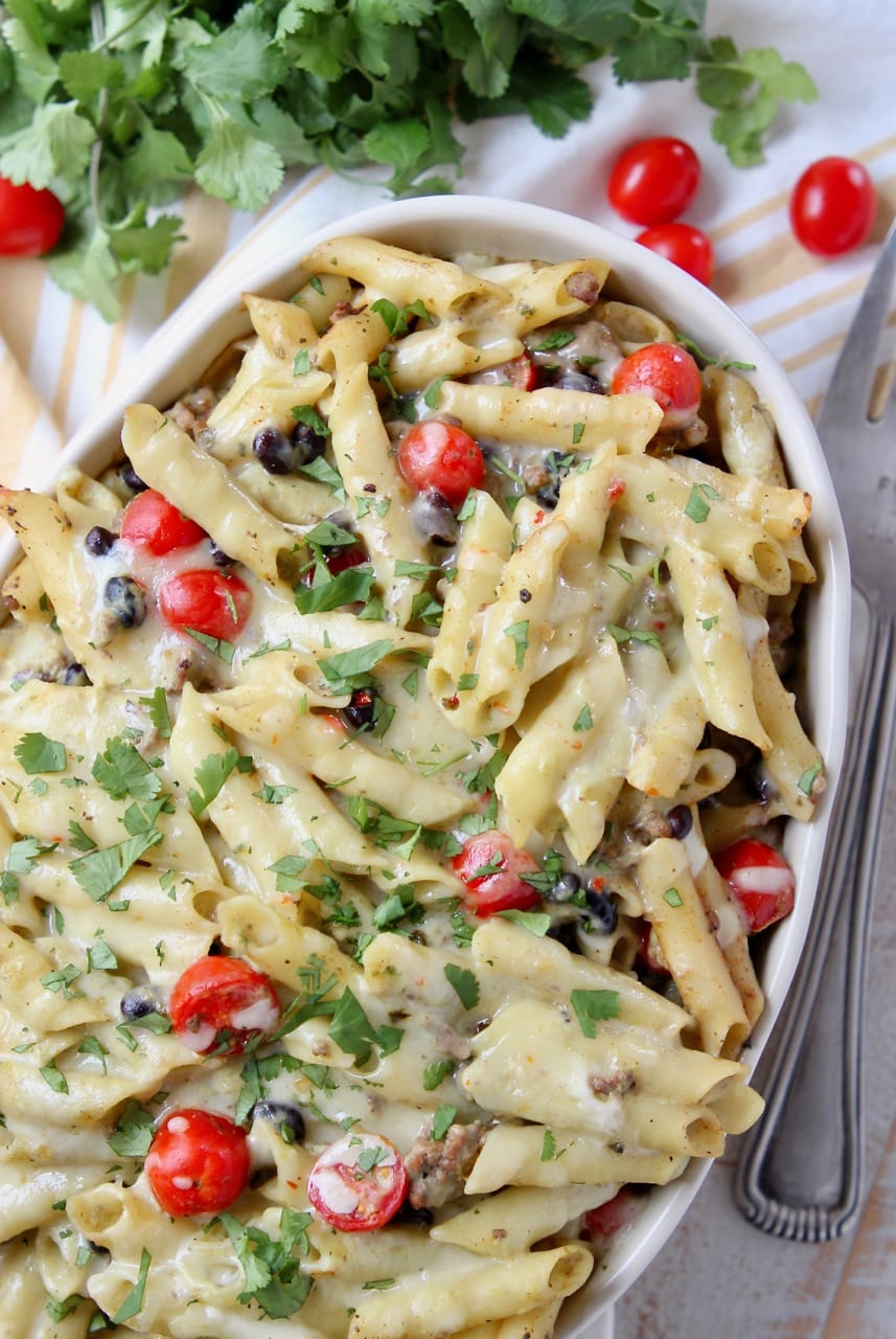 Baked taco pasta in a casserole dish with black beans, cherry tomatoes and cilantro