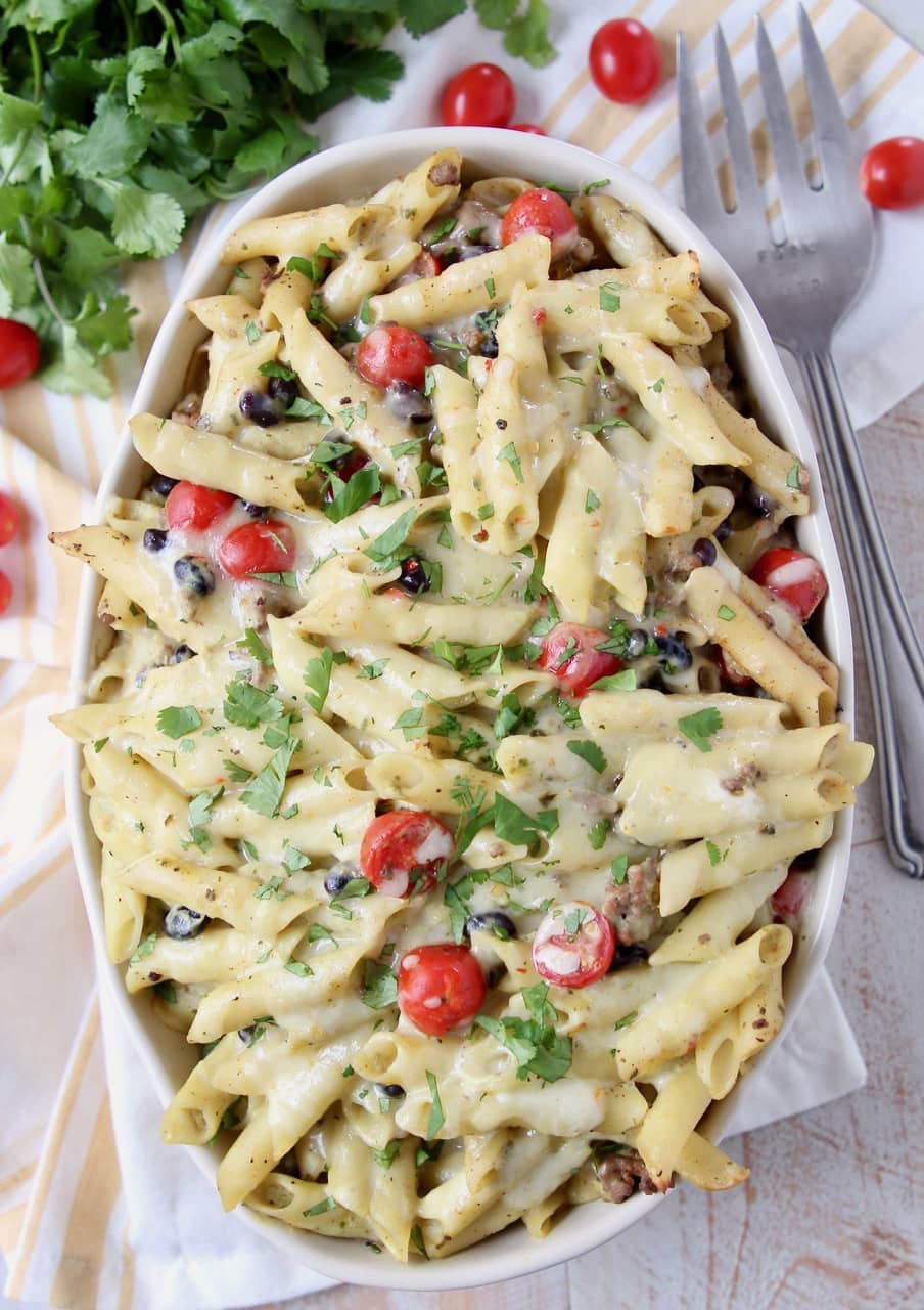 Taco pasta in a large oval casserole dish topped with cherry tomatoes and cilantro