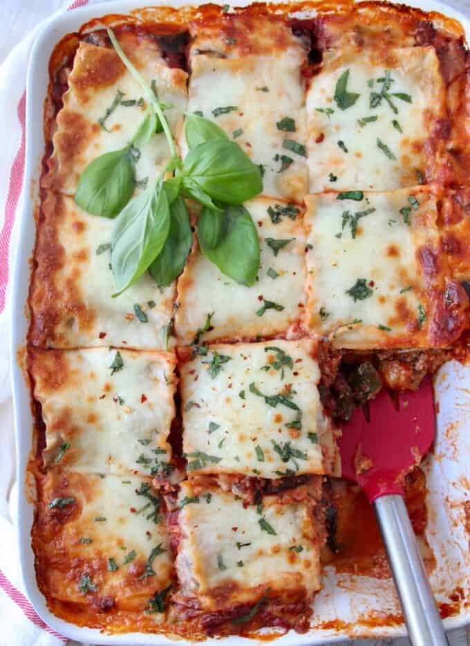 overhead image of lasagna in casserole dish cut into squares with red spatula