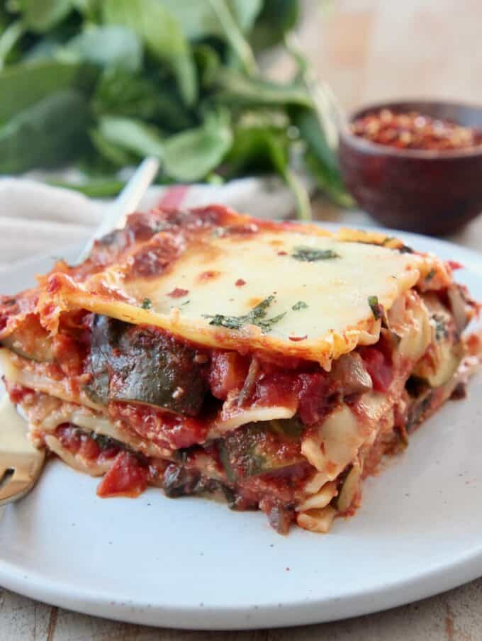 slice of vegetable lasagna on plate with fork