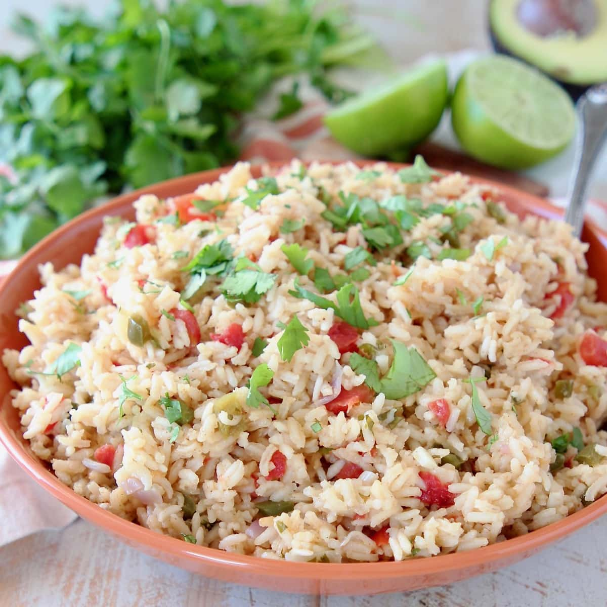 Mexican rice in orange bowl with cilantro and limes