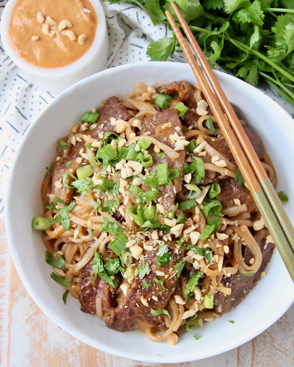 Thai beef and noodles in white bowl, topped with diced green onions