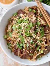 Overhead shot of sliced beef and noodles in bowl with chopsticks on the side