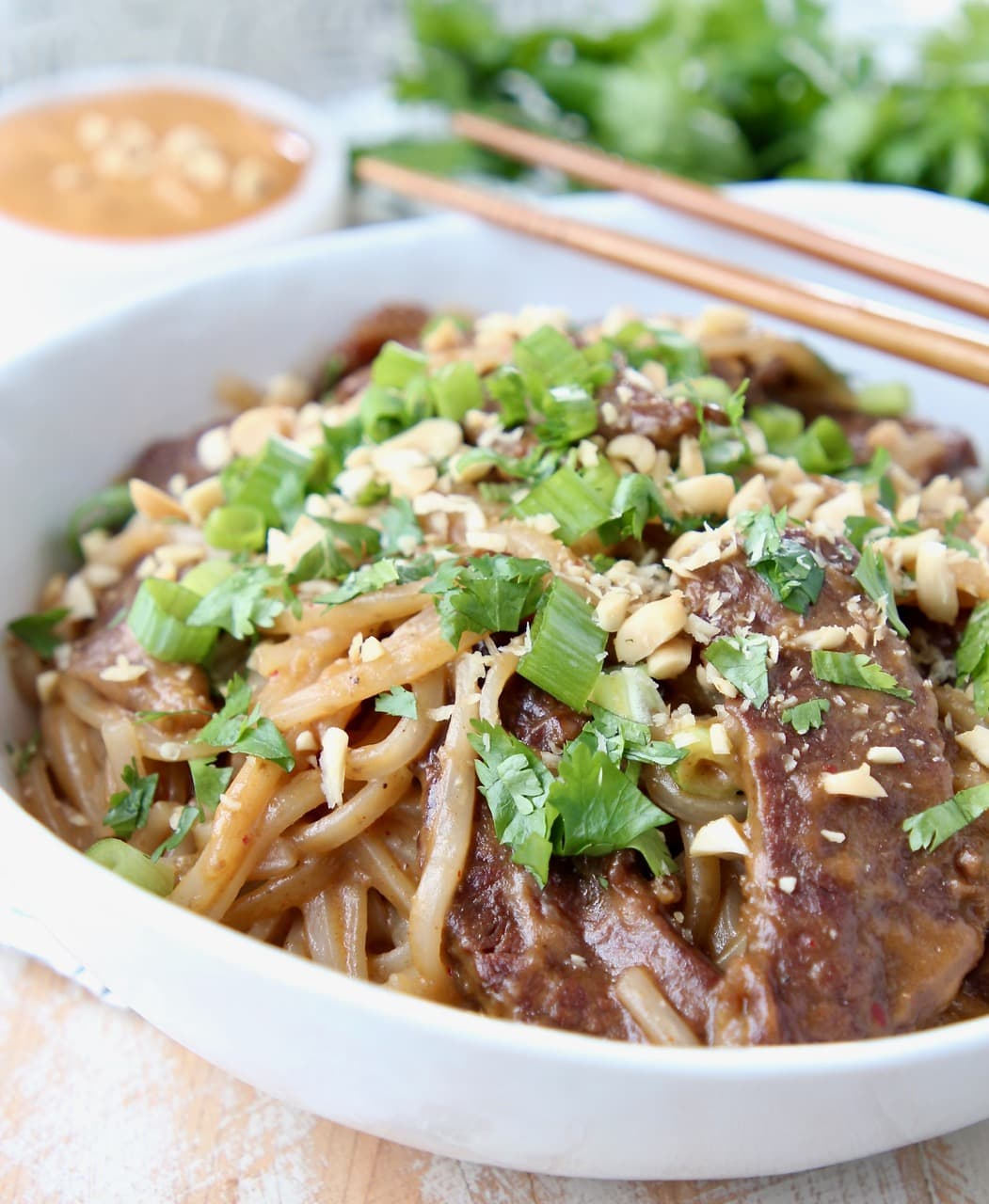 Sliced beef, noodles and sliced green onions in bowl with chopsticks on the side