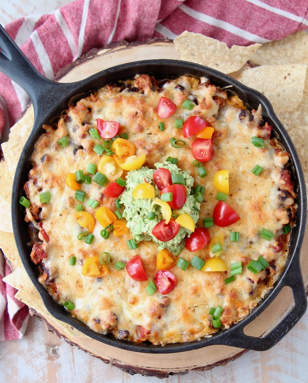 Overhead shot of cheesy taco dip baked in a cast iron skillet topped with diced cherry tomatoes and guacamole