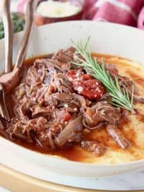 Shredded beef ragu tomato sauce in bowl with creamy polenta and rosemary sprig