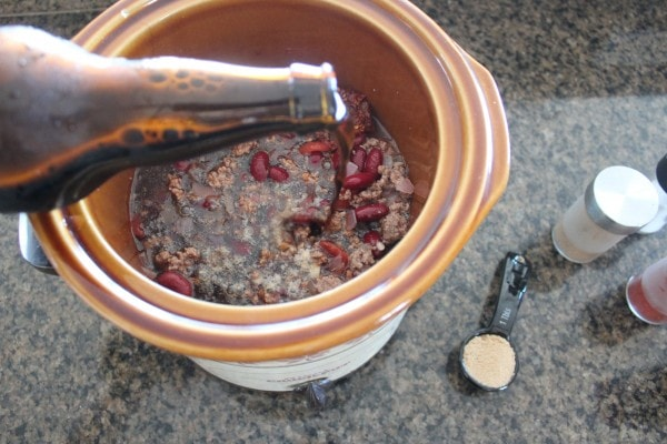 beer being poured into a slow cooker filled with meat and beans.