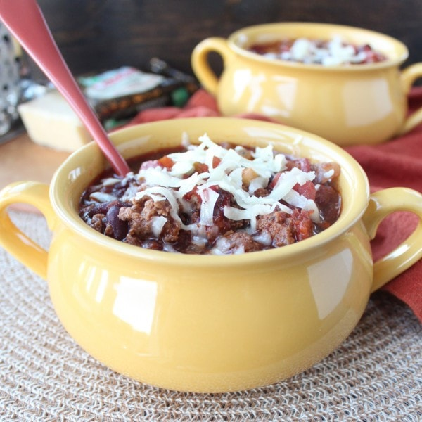 Yellow bowl filled with chili with a red spoon