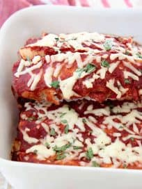 Enchilada with red sauce lifted out of white baking dish with spatula