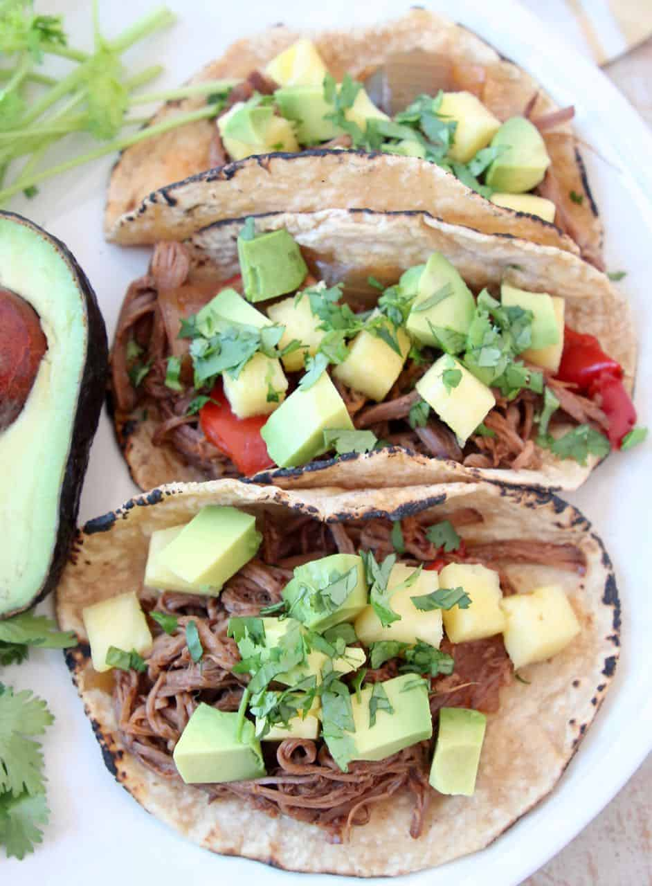 Three shredded tri tip tacos on plate with avocado