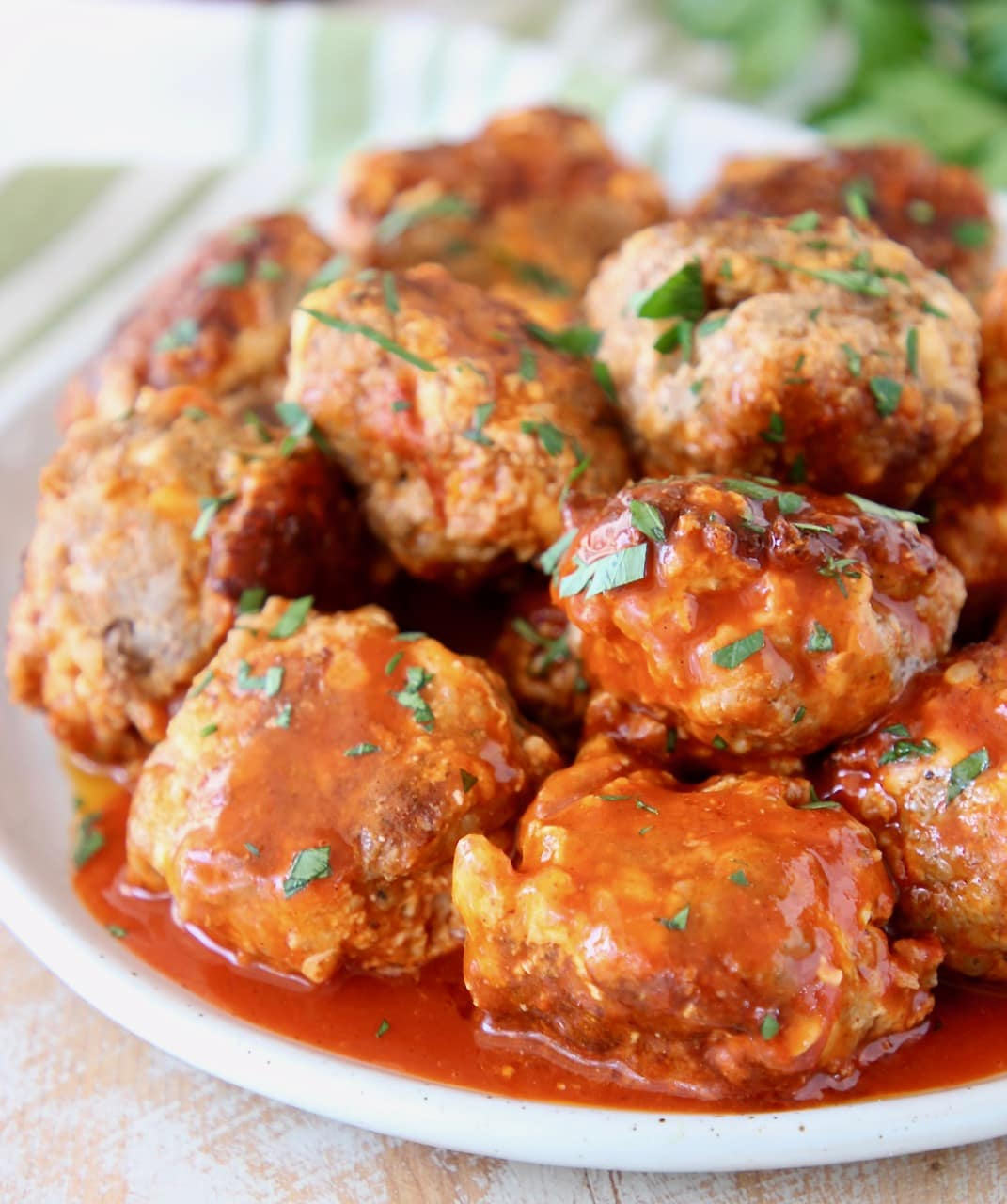 Cheesy Sausage Balls with Buffalo Sauce and Cilantro Garnish on Plate with Green Striped Towel