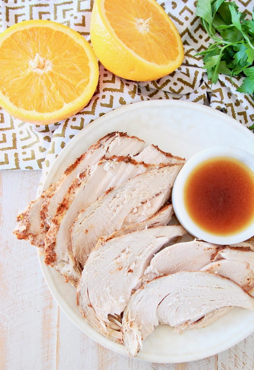 Slices of spice rubbed turkey breast on plate, next to small white bowl or orange bourbon sauce, with an orange cut in half next to the plate with fresh parsley