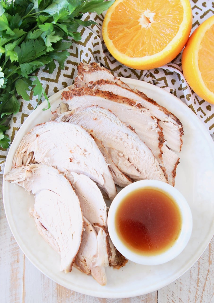 Slices of turkey breast on a white plate, with a side ramekin of orange bourbon glaze with sliced orange in background and fresh parsley bunch