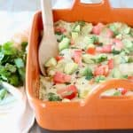 Mexican casserole in orange baking dish with wooden spoon
