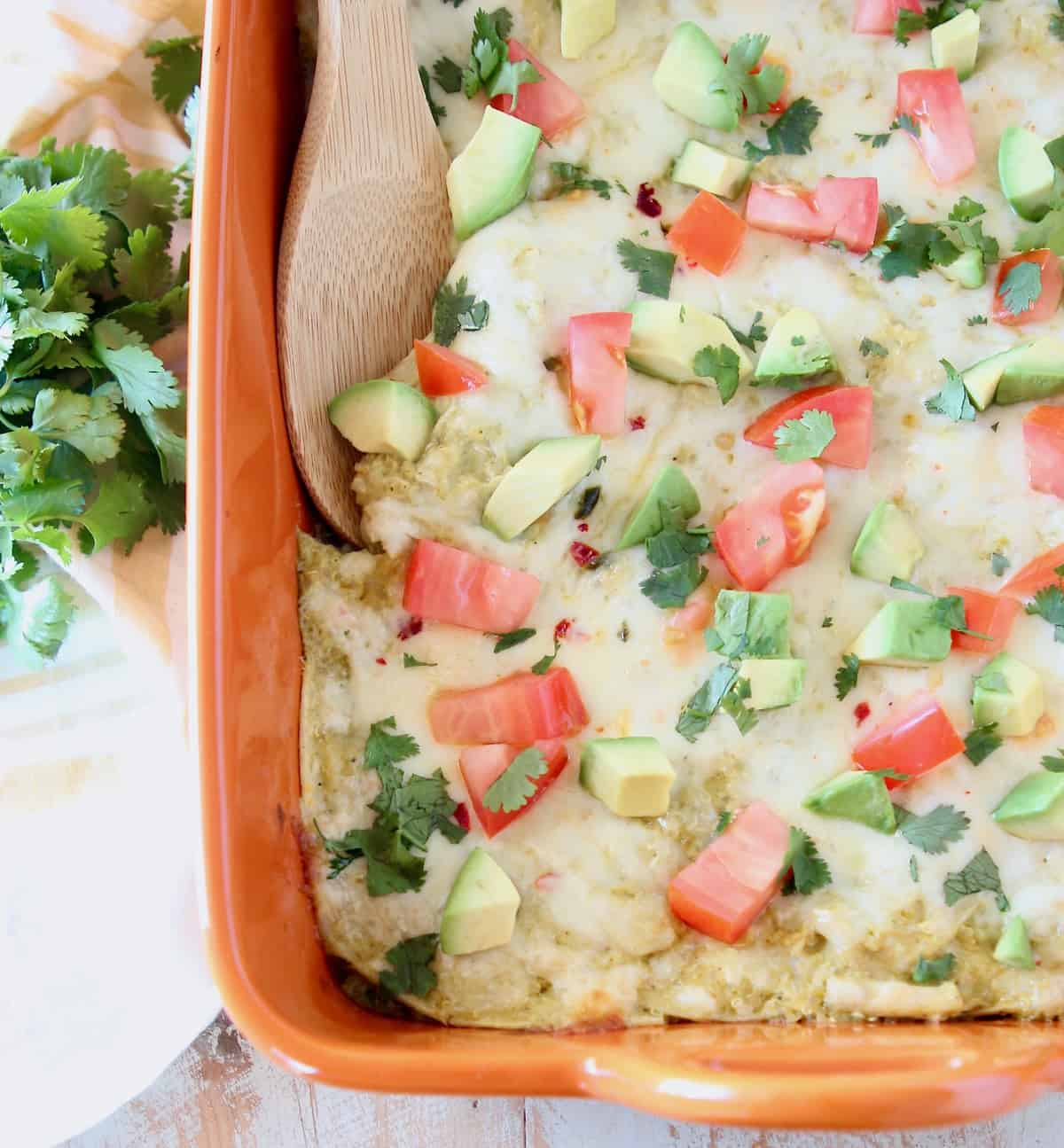 Chicken enchilada casserole topped with diced tomatoes and avocado