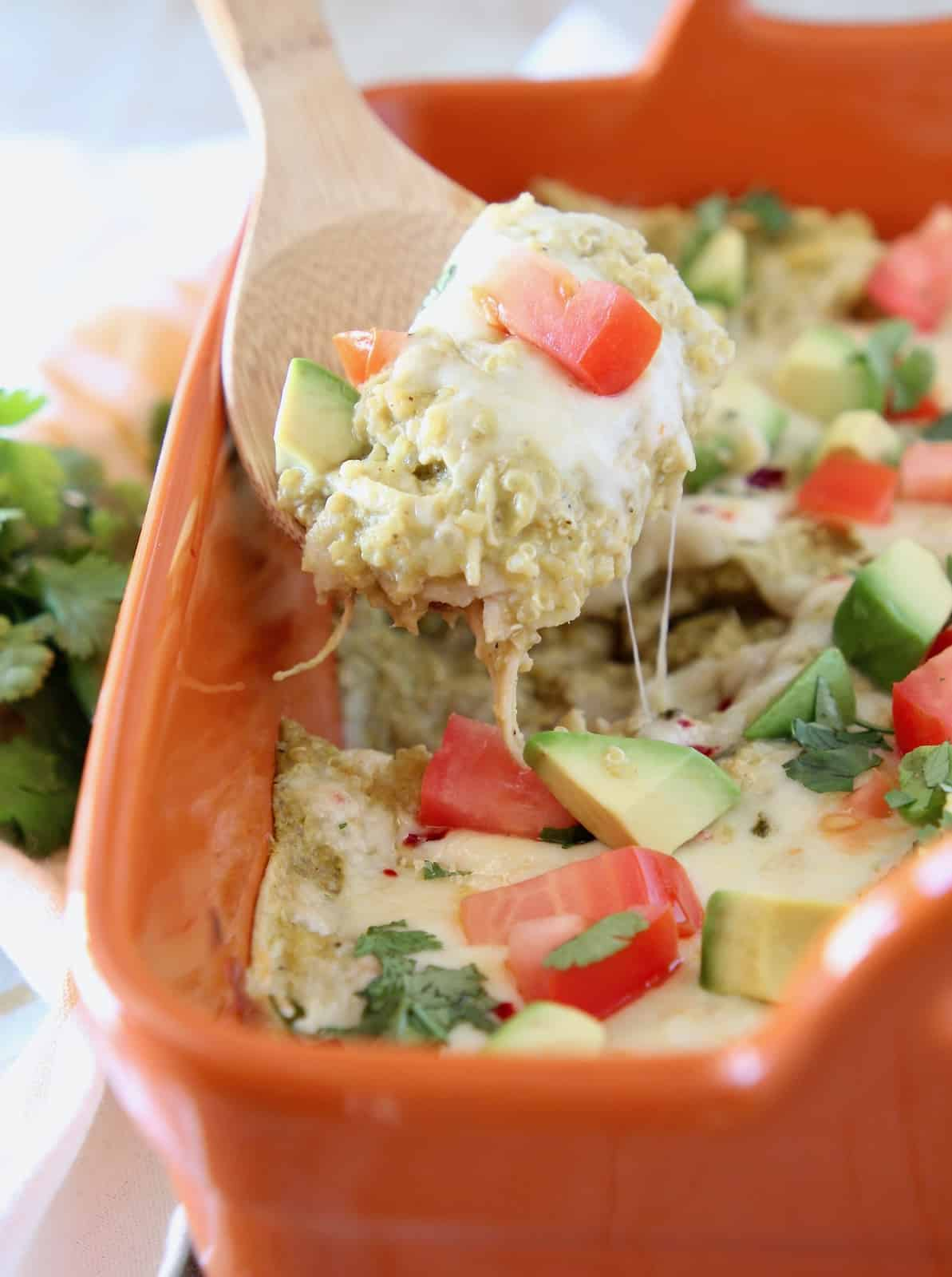 Wooden spoon of quinoa chicken enchilada casserole, topped with cheese and diced tomatoes