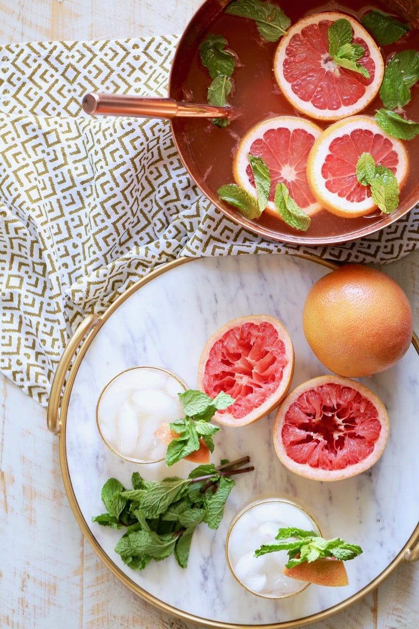 Rum punch in copper bowl with fresh grapefruit slices and mint springs, with a marble serving tray sitting next to it, topped with glasses of rum punch, grapefruits sliced open and fresh mint sprigs