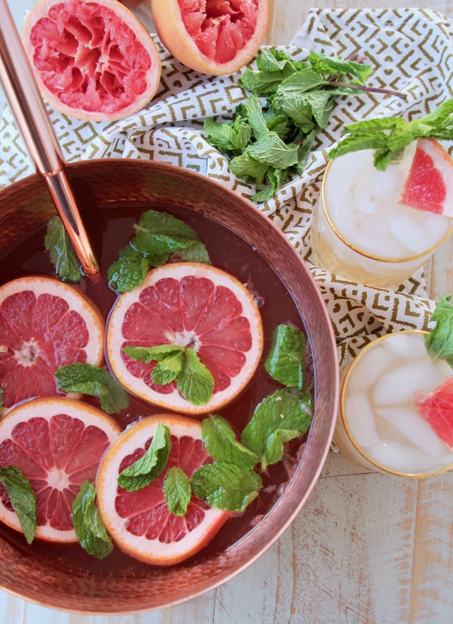Copper serving bowl filled with spiced rum punch, topped with slices of grapefruit and mint leaves, with two glasses of rum punch on the side sitting on a patterned towel with fresh mint leaves
