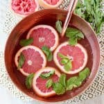Spiced rum punch in copper bowl, topped with fresh grapefruit slices and fresh mint leaves, with rose gold ladle and fresh mint leaves on the side