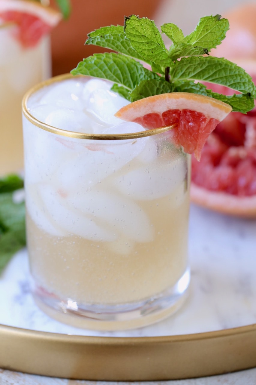 Grapefruit Ginger Rum Punch in glass with grapefruit slice on side and fresh mint in glass with ice