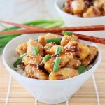 Chinese honey chicken in white bowl with brown chopsticks and green onions