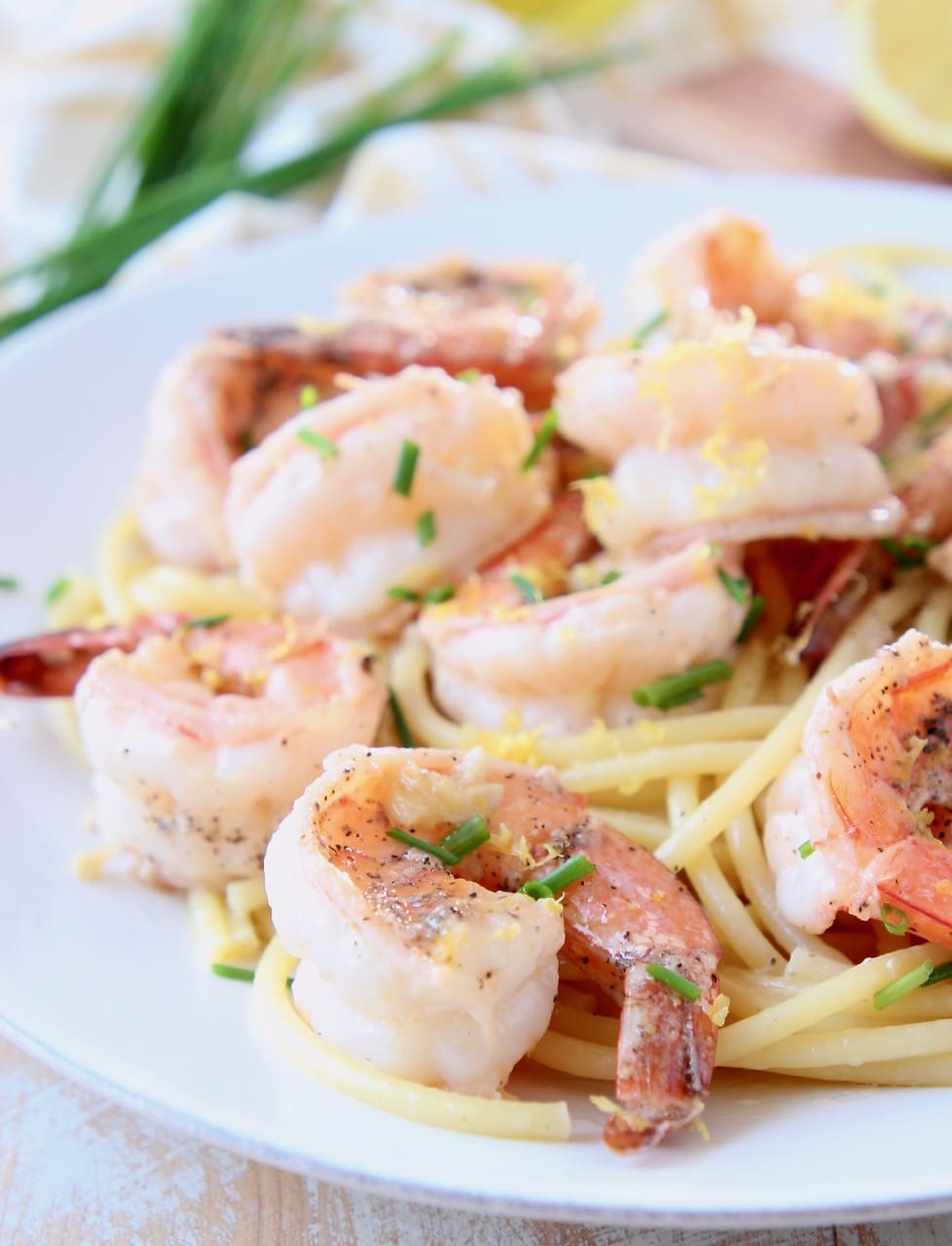 Shrimp scampi on top of bucatini pasta on white plate